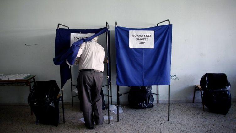 Un homme vote lors des élections législatives à Athènes (Grèce), le 6 mai 2012. (ANGELOS TZORTZINIS / AFP)