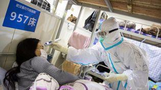 Un médecin prend la température d'une patiente, dans un hôpital de Wuhan, dans la province de Hubei, dans le centre de la Chine, lundi 17 février 2020. (AFP)