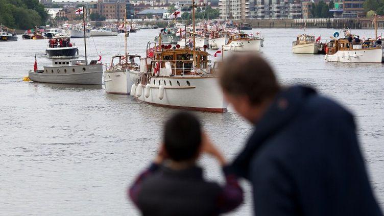 Des passants observent les bateaux qui participeront à la parade prévue pour le jubilé de la reine Elizabeth II samedi 2 juin sur la Tamise, à Londres (Royaume-Uni). (ANDREW COWIE / AFP)