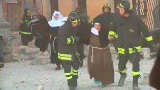 Des religieuses secourues par les pompiers, après l'effondrement de la basilique Saint-Benoît détruite par le séisme à Norcia (Italie), le 30 octobre 2016. (AP / SKY ITALIA)