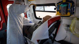 Un pompier procure des soins à un homme suspecté d'avoir le coronavirus, le 6 avril 2020, à Marseille. (CHRISTOPHE SIMON / AFP)