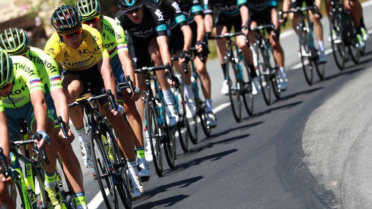 """Le Slovaque Peter Sagan porte encore le maillot jaune dans le peloton,avec ses coéquipiers de l'équipe russe """"Tinkoff""""lors dela cinquième étape du Tour de France,entre Limoges et Lioran,le 6 juillet 2016. (KENZO TRIBOUILLARD / AFP)"""