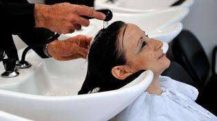 Les cheveux d'une femme vont être lavés avant qu'elle soit coiffée. (PHILIPPE HUGUEN / AFP)