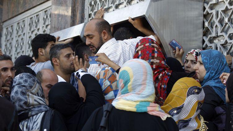 Des Gazaouis se ruent sur les distributeurs de banques pendant les cinq heurs de trêve, à Gaza, le 17 juillet 2014. (MOHAMMED ABED / AFP)