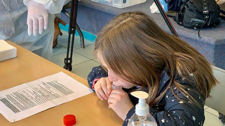 Une fillette réalise un test salivaire dans une école du Pas-de-Calais, le 8 mars 2021. (CLAIRE MESUREUR / FRANCE-BLEU NORD)