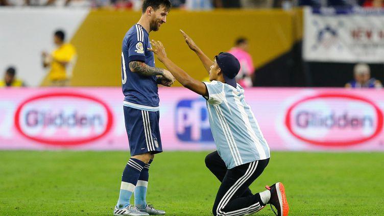 La star de l'Argentine Lionel Messi avec un fan rentré sur le terrain lors du match contre les Etats-Unis  (BOB LEVEY / GETTY IMAGES NORTH AMERICA)