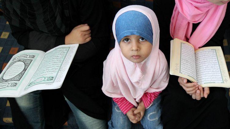 Des femmes accompagnées d'une fillette lisent le Coran dans une mosquée à Tripoli, la capitale de la Libye, le 12 octobre 2011. (KARIM SAHIB/AFP)