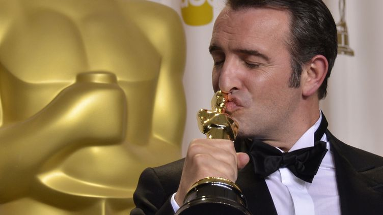 """Jean Dujardin embrasse son Oscar du meilleur acteur reçu dimanche 26 février à Los Angeles pour son rôle dans """"The Artist"""". (JOE KLAMAR / AFP)"""