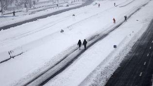 Des personnes marchent le long de l'autoroute M-30, à Madrid, le 9 janvier 2021. (BURAK AKBULUT / ANADOLU AGENCY / AFP)