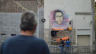 Un passant devant la fresque dévoilée d'Aïcha Issadounène par C215 à Saint-Ouen. (VICTOR VASSEUR / FRANCE-INFO)