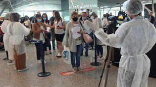 Des agents de santé tunisiens contrôlent les touristes européens à leur arrivée à l'aéroport international d'Enfidha-Hammamet, près de la ville méditerranéenne de Sousse, le 22 mai 2021. (FETHI BELAID / AFP)