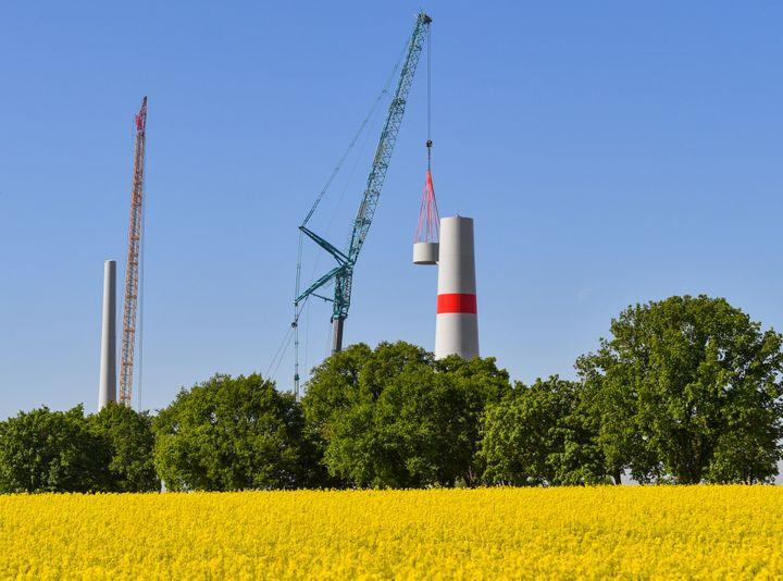 Un morceau d'acier est ajouté lors de la construction d'une éolienne, àMallnow (Allemagne) le 7 mai 2018. (PATRICK PLEUL / DPA-ZENTRALBILD / AFP)
