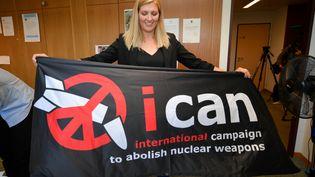 Béatrice Fihn, la directrice de l'Ican, la Campagne internationale pour l'abolition des armes nucléaires, brandit un drapeau de sa coalition d'ONG pour célébrer le prix Nobel de la paix décerné à son organisation, le 6 octobre 2017 à Genève (Suisse). (FABRICE COFFRINI / AFP)