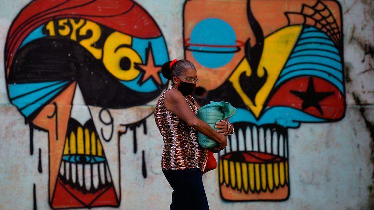 Une passante devant une peinture murale de La Havane, le 2 décembre 2020. (YAMIL LAGE / AFP)
