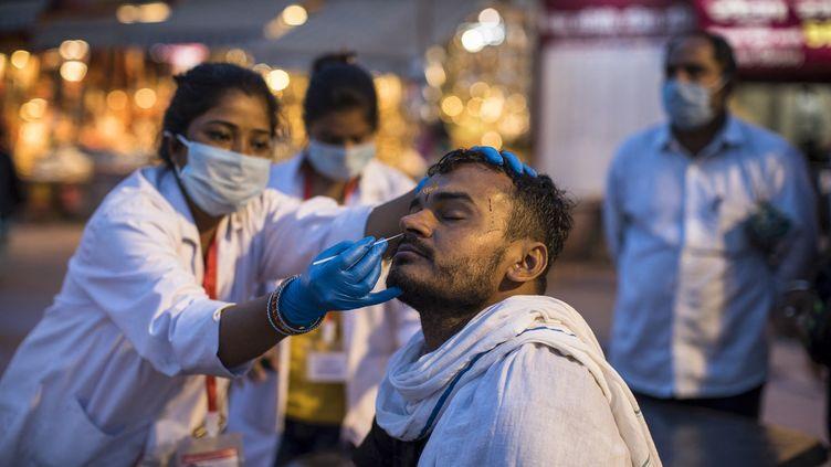 Un participant du pèlerinage de la Kumbh Mela, à Haridwar (Inde) subit un test anti Covid-19 le 12 avril 2021 (XAVIER GALIANA / AFP)