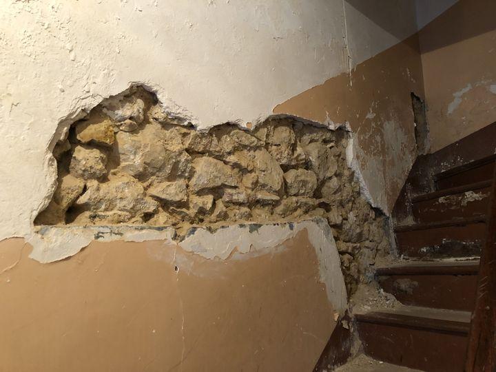Au 40 rue du Bruys, dans le centre-ville de Marseille, le mur du hall d'entrée s'effondre sur l'escalier. (MATHILDE GOUPIL / FRANCEINFO)