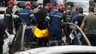 """Les pompiers transportentun sac mortuaire dans le village de Mati, près d'Athènes, mardi 24 juillet 2018. Dans cette station balnéaire, un groupe de 26 personnes a été retrouvé enlacé,""""dans une dernière tentative pour se protéger"""", a raconté un sauveteur, Vassilis Andriopoulos. (AYHAN MEHMET / ANADOLU AGENCY)"""
