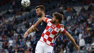 Le défenseur écossaisGrant Hanley au duel aérien avec l'attaquant de la Croatie,Bruno Petkovic, le 22 juin 2021 à l'Euro. (LEE SMITH / POOL / AFP)