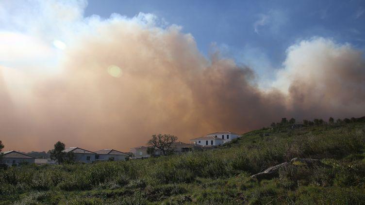 Un nuage du fumée s'approche des habitations à Biguglia (Haute-Corse), où un incendie faitrage lors du passage de la tempête Ciara, le 11 février 2020. (PASCAL POCHARD-CASABIANCA / AFP)