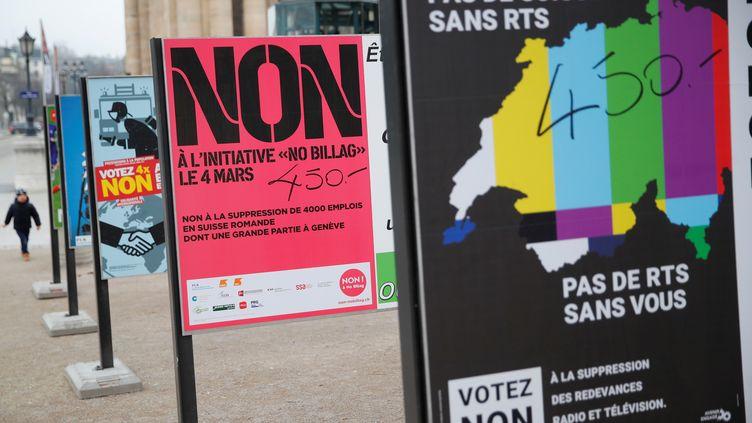 """Des panneaux appelant à voter """"non"""" à la votation sur la suppression de la redevance audiovisuelle, le 9 février 2018, à Genève (Suisse). (DENIS BALIBOUSE / REUTERS)"""