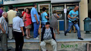 Des Grecs attendent de pouvoir retirer de l'argent à un distributeur automatique de billets, le 8 juillet 2015, à Athènes (Grèce). (SAKIS MITROLIDIS / AFP)