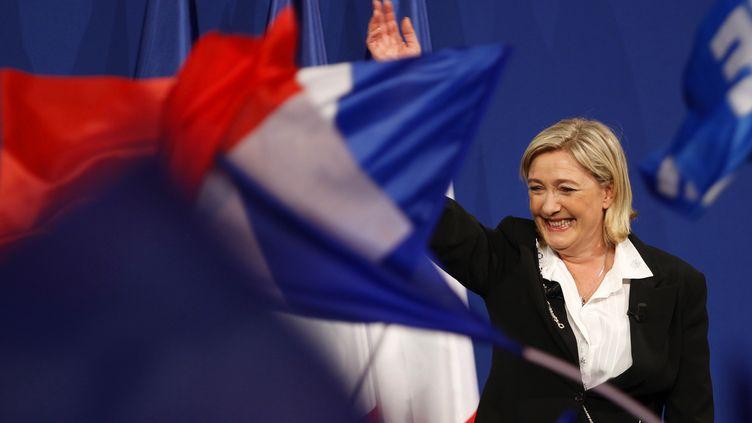 La présidente du FN, Marine Le Pen, salue ses partisans après l'annonce des résultats du premier tour de l'élection présidentielle, le 22 avril 2012 à Paris. (FRANCOIS GUILLOT / AFP)