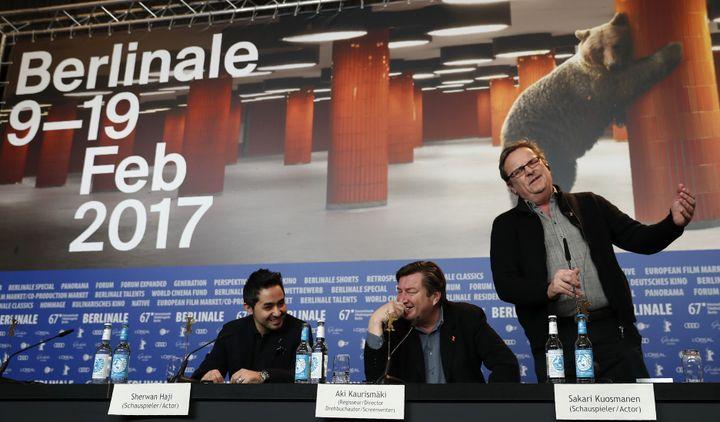 """Le comédien syrien Sherwan Haji, le cinéaste Aki Kaurismäki et le comédien et chanteur finlandais Sakari Kuosmanen s'amusant à chanter une chanson finlandaise lors de la conférence de presse autour du film """"L'autre côté de l'espoir""""le 14 février 2017.  (Odd ANDERSEN / AFP)"""