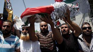 Des manifestants palestiniens portent le corps d'un bébé palestinien, mort dans l'incendie de sa maison provoqué par des colons israéliens, le 31 juillet 2015, dans le village de Douma, en Cisjordanie occupée. (THOMAS COEX / AFP)