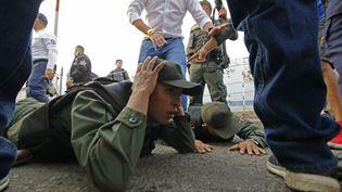 Des soldats vénézuéliens allongés sur le sol après avoir déserté pour passer en Colombie, le 23 février 2019. (SCHNEYDER MENDOZA / AFP)