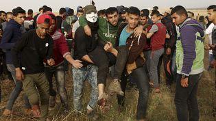 """Des Palestiniens évacuent un blessé lors de rassemblements qui ont suivi la """"marche du retour"""" dans la bande de Gaza, le 5 avril 2018. (ADEL HANA/AP)"""