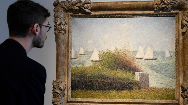 """Un homme regarde le tableau """"La rade de Grancamp"""" (1877)peint par Georges Seurat et qui fait partie de la collection Rockefeller.  (BERTRAND GUAY / AFP)"""
