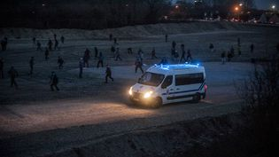 Des migrants jettent des pierres sur un camion de police, à Calais (Pas-de-Calais), le 29 février 2016. (JULIEN PITINOME / AFP)