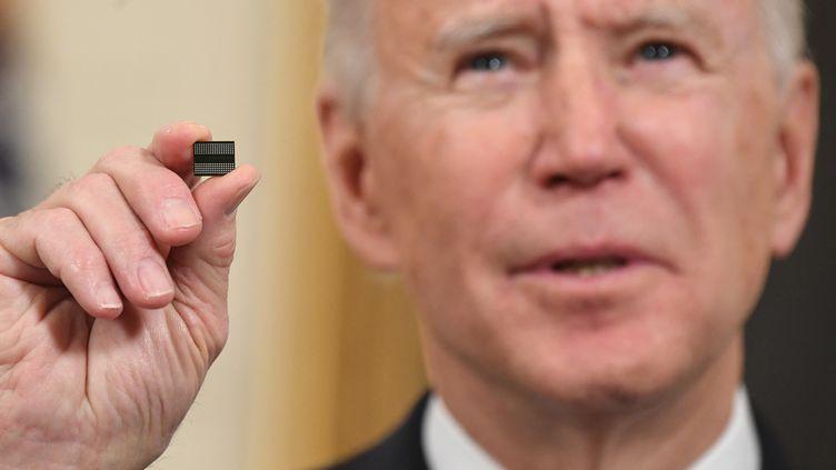 Le président des États-Unis Joe Biden montre une puce électronique le 24 février à la Maison Blanche, lorsqu'il annonce un décret visant à réduire la tension mondiale sur le marché des composants électroniques. (SAUL LOEB / AFP)