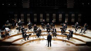 Les musiciens de l'Orchestre de Paris ont recommencé à jouer ensemble dans la salle Pierre Boulez de la Philharmonie, mais à distance et devant des gradins vides (27 mai 2020) (FRANCOIS GUILLOT / AFP)