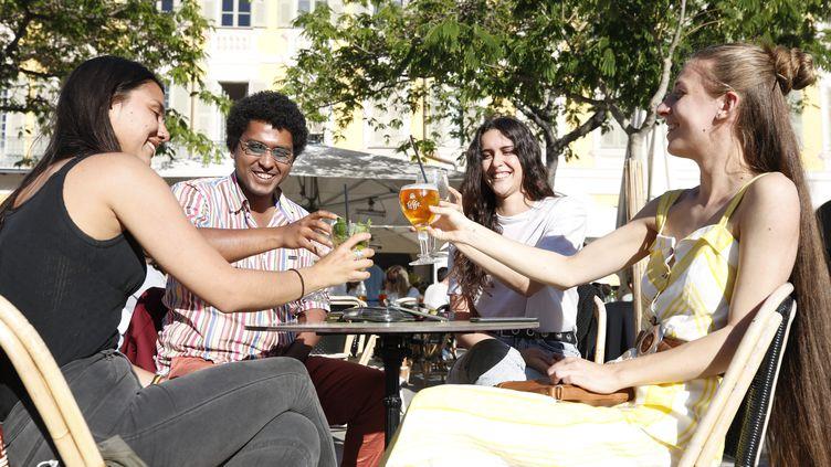 Des jeunes autour d'une table sur une terrasse d'un café à Nice (Alpees-Maritimes). (DYLAN MEIFFRET / MAXPPP)