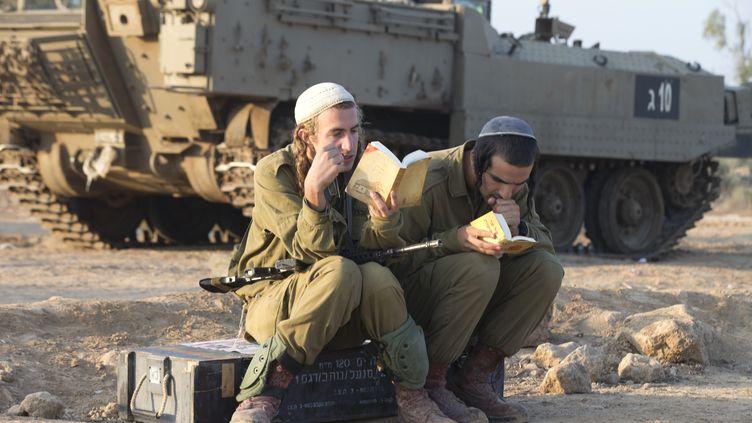 Deux soldats israéliens réservistes pendant leur prière du matin,le 20 novembre 2012,près de la frontière entre Israël et la bande de Gaza. (JACK GUEZ / AFP)