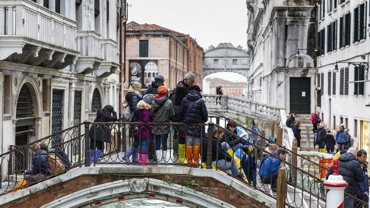 Des touristes s'amassent sur un pont de Venise, le 17 novembre 2019. (MARCO SERENA / NURPHOTO / AFP)
