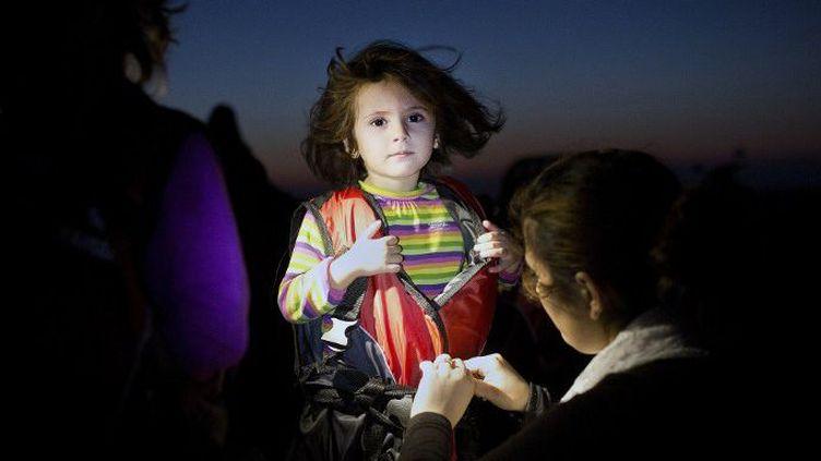 Kos, le 13 août 2015. Symbole de l'immigration qui arrive en Grèce, cette fillette, tout juste débarquée de son canot en provenance de Turquie, se fait enlever son gilet de sauvetage. (ANGELOS TZORTZINIS / AFP)