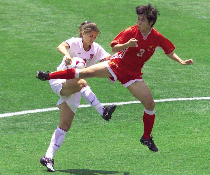 La star américaine Mia Hamm à la lutte sur un ballon avec la défenseuse chinoise Fan Yunjie, en finale de la Coupe du monde, le 10 juillet 1999 à Padadena (Californie). (HECTOR MATA / AFP)