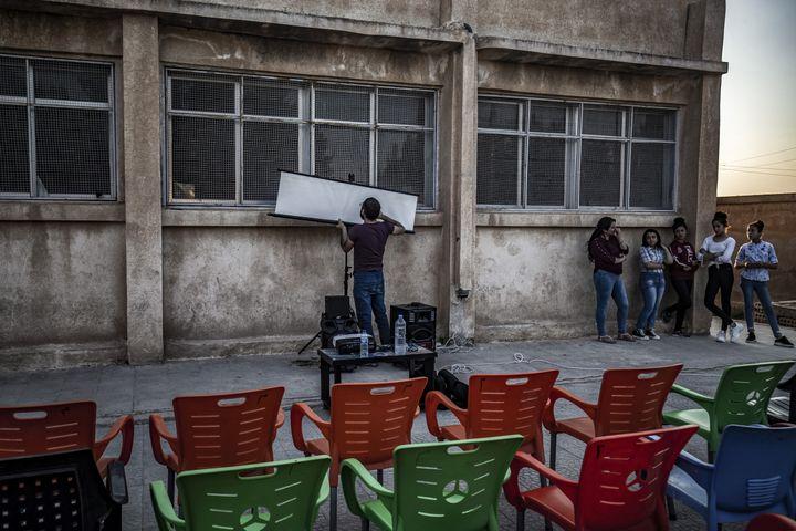 Un membre du cinéma itinérant du réalisateur Shero Hinde installe un écran de cinéma. (DELIL SOULEIMAN / AFP)
