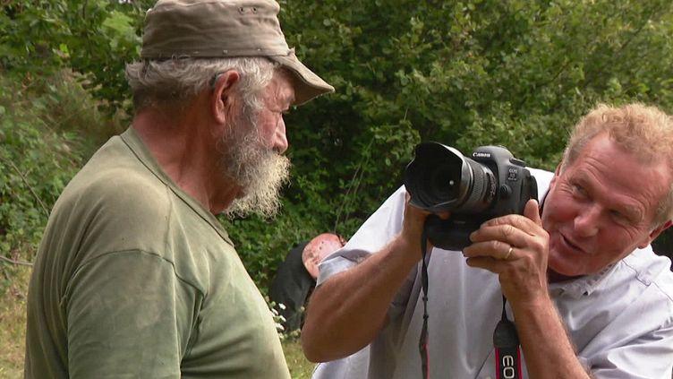 Le photographe Claude Fougeirol en pleine séance photo avec un agriculteur ardéchois. (FRANCEINFO)