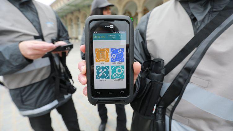 Les agents chargés de la verbalisation présentent leur appareil pour dresser les forfaits post-stationnement, à Paris, le 6 décembre 2017. (MAXPPP)