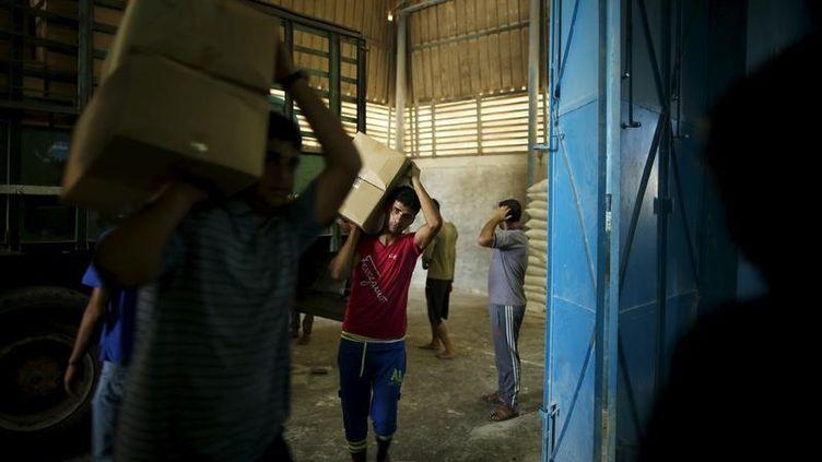 Des travailleurs palestiniens transportent des cartons d'aide alimentaire, le 22 septembre 2015 à Gaza. (MOHAMMED SALEM / REUTERS / X01571)