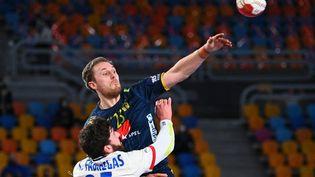 Le Français Ludovic Fabregas et le Suédois Albin Lagergren lors de la rencontre en demi-finales du Mondial de handball entre leurs deux pays, le 29 janvier 2021 au Caire. (ANNE-CHRISTINE POUJOULAT / AFP)