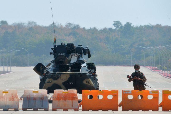 Un soldat monte la garde aux côtés d'un char de l'armée birmane sur la route qui mène au Parlement, à Naypyidaw, le 1er février 2021. (STR / AFP)