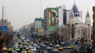 La cathédrale arménienne Saint Sarkis, à côté d'un bâtiment sur lequel se trouve un portrait del'ayatollah Ruhollah Khomeini, le 1er janvier 2020 à Téhéran (Iran). (ATTA KENARE / AFP)