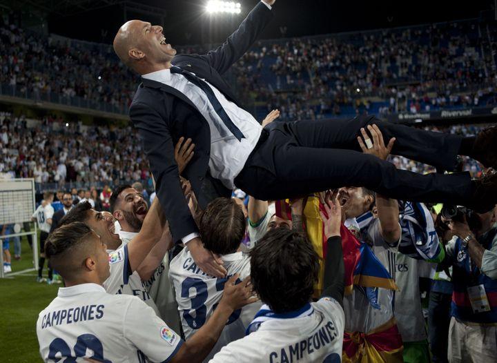 Zinedine Zidane porté en triomphe par ses joueurs du Real Madrid après le titre de champion d'Espagne 2016-2017 (SERGIO CAMACHO / AFP)