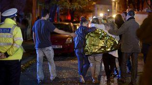 Des jeunes gens sortent de la discothèque où une explosion a tué au moins 27 personnes, à Bucarest (Roumanie), le 31 octobre 2015. (REUTERS)