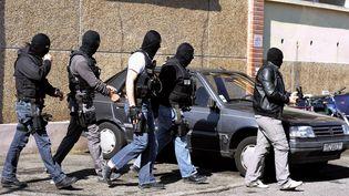Des policiers devant l'appartement où a été donné l'assaut contre Mohamed Merah à Toulouse, le 23 mars 2012. (JEAN-PIERRE MULLER / AFP)