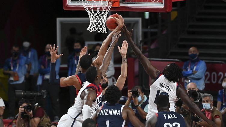 Le Français Timothe Luwawu Kongbo (G) à la lutte avec l'Américain Jrue Holiday (D) lors de la finale olympique du basket à Tokyo (Japon), le 7 août 2021. (MOHD RASFAN / AFP)